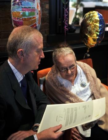 Per šimtąjį gimtadienį klausosi W.Hague sveikinimo, kurį skaito britų konsulas Honkonge. AFP-Scanpix nuotr.